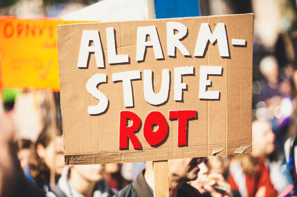 """Wie funktioniert effektive Klimakommunikation? Ein Plakat """"Alarmstufe Rot"""" auf einem Klimaprotest."""
